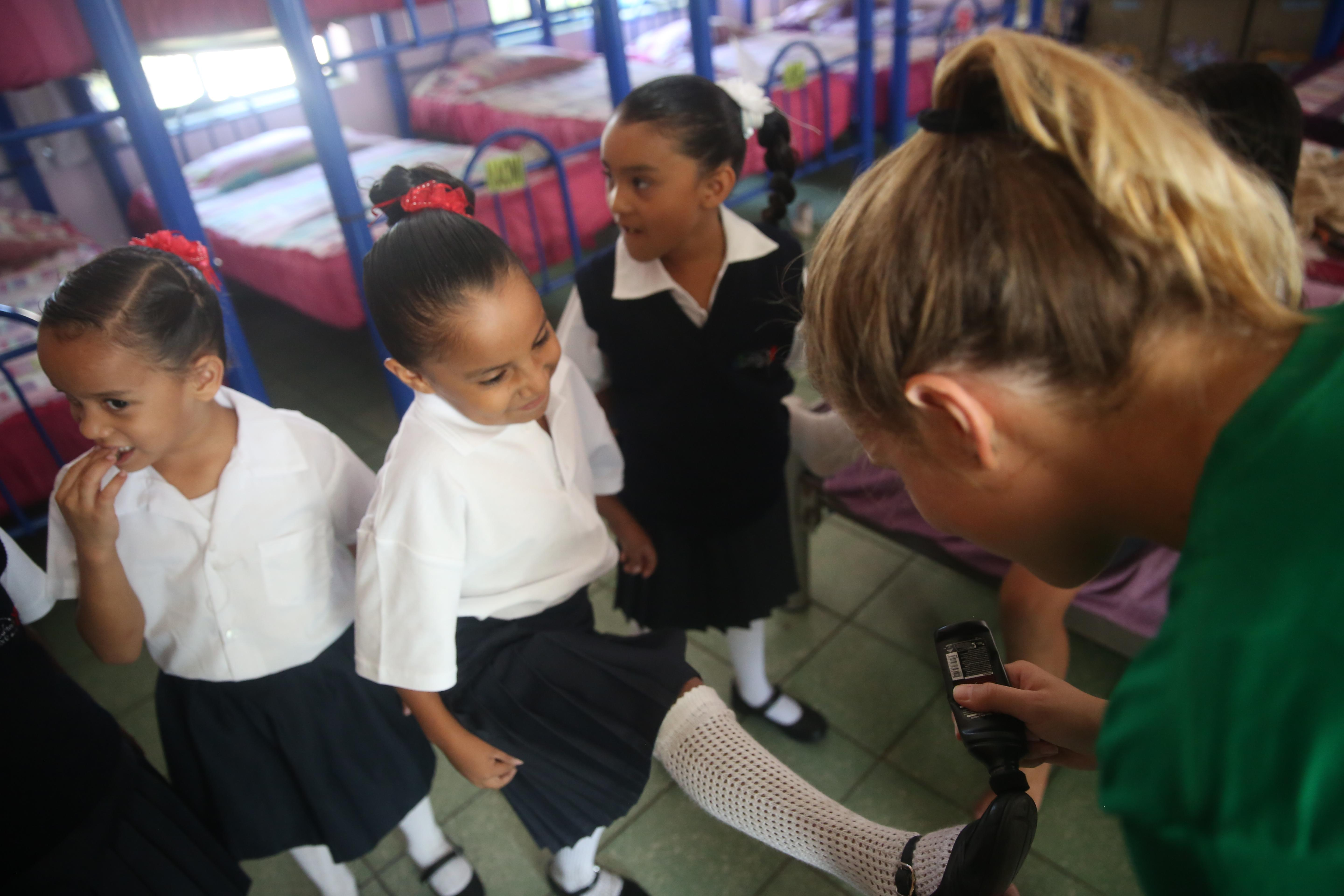 Projects Abroad volunteer working with children in Mexico polishes a young girl's shoes at her Childcare placement.